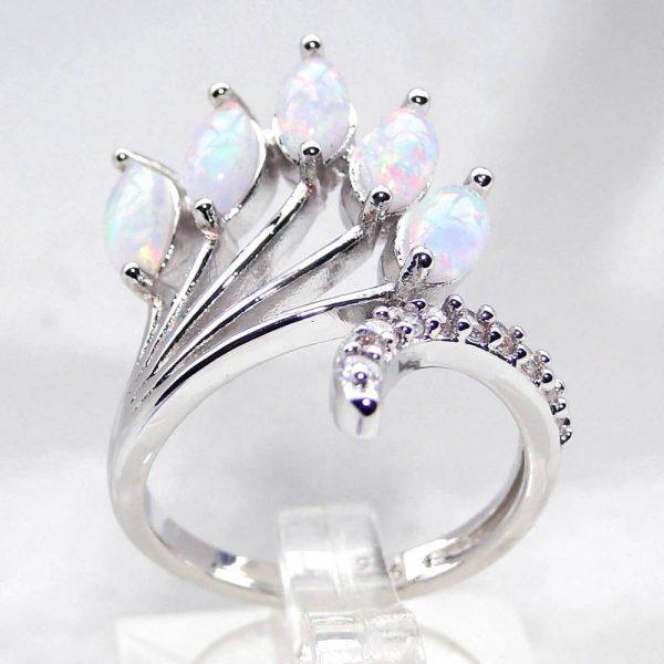 детайлен фронтален кадър на сребърен пръстен с пет отделни камъка синтетичен опал и малки кристали по основната част на пръстена