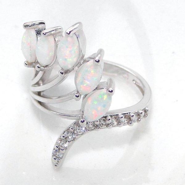 сребърен пръстен с пет отделни камъка синтетичен опал и малки кристали по основната част на пръстена сниман на бял фон