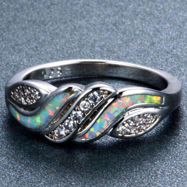 Сребърен пръстен с изключително цветен синтетичен опал и сребърни камъчета сниман легнал върху тъмна повърхност