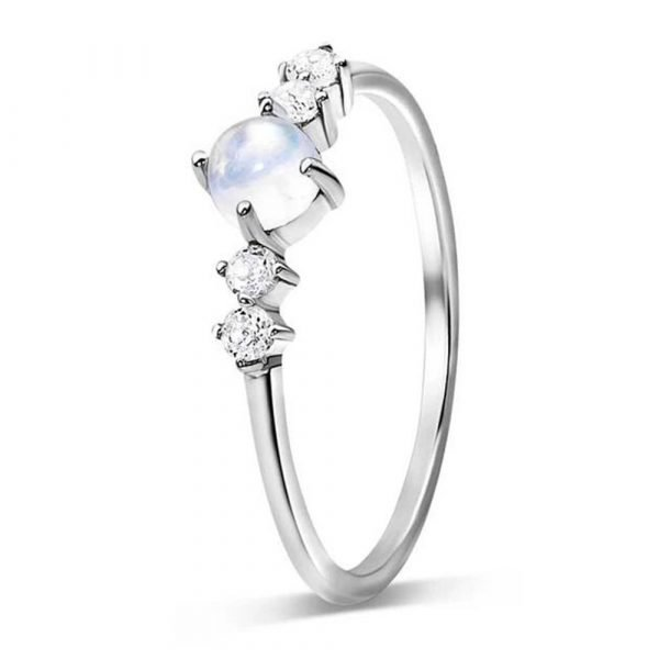 aesthetic silver ring with a natural moonstone in the middle and two small crystals on each side of it photographed close up against a white background