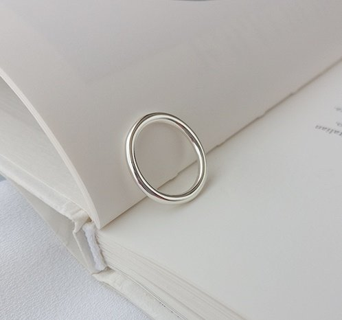 clean silver ring type ring photographed on a book page