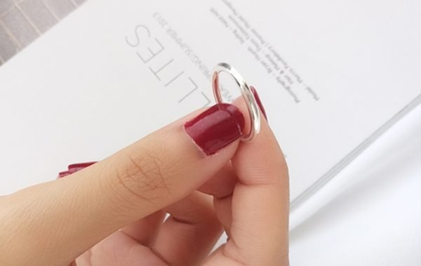 ladies hand holding a clear silver ring type ring