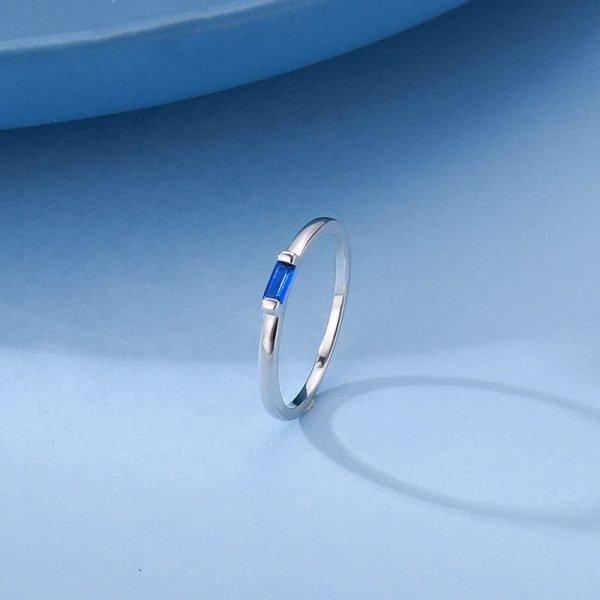 сребърен пръстен с правоъгълен син кубичен цирконий в центъра сниман върху синя повърхност