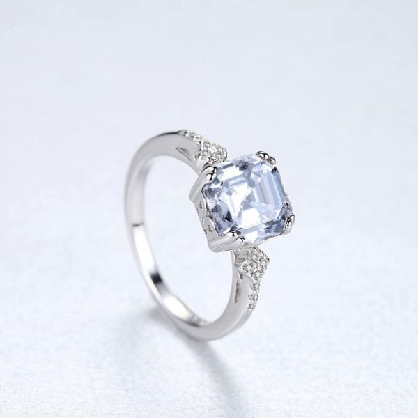 silver ring with massive cubic zirconia photographed at a slight angle on a light blue background