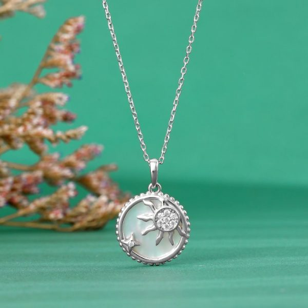 silver necklace with round pendant depicting sun and star photographed frontally on greenish background