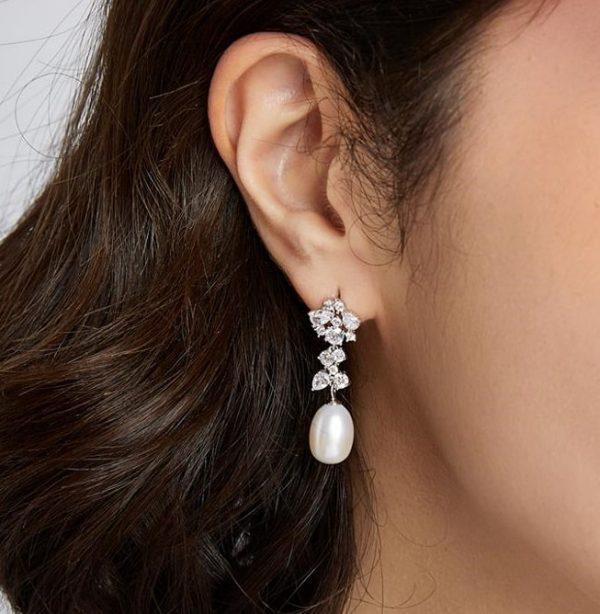 side shot of model wearing dangling pearl earrings with floral motif