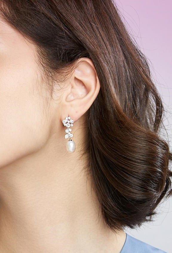 side shot of female model wearing dangling pearl earrings with floral motif