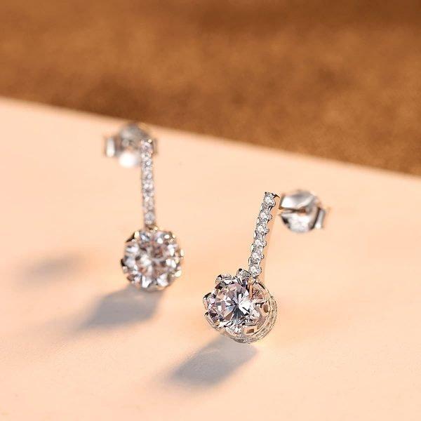 сребърни дроп обеци с малки камъчета и масивен кръгъл циркон - снимка с фокус върху едната обеца