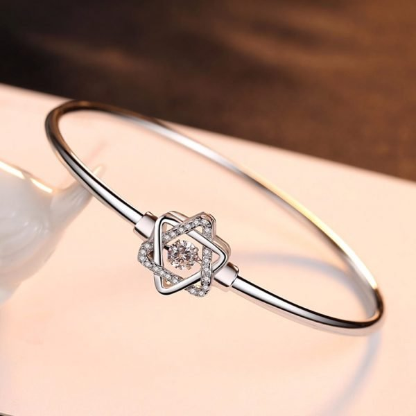 solid silver bracelet with star-shaped element and cubic zirconia in the middle photographed at a slight angle on a white surface