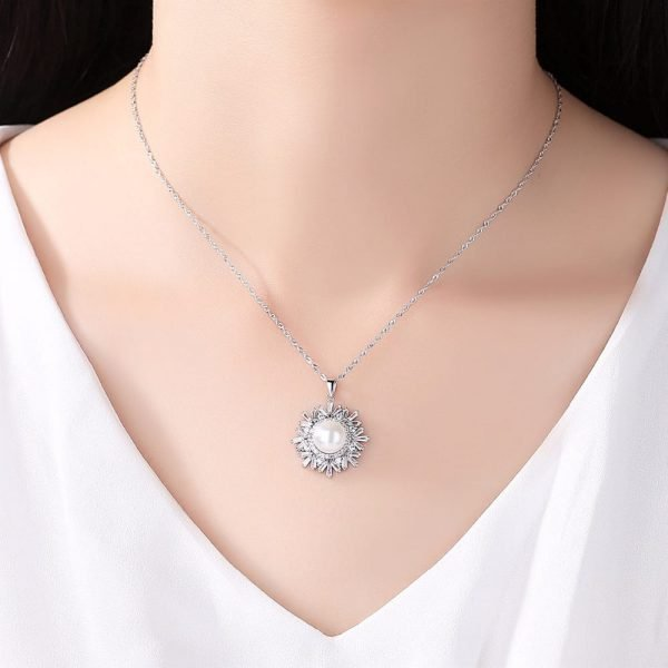 ladies model with silver necklace with massive pearl surrounded by many cubic zircons