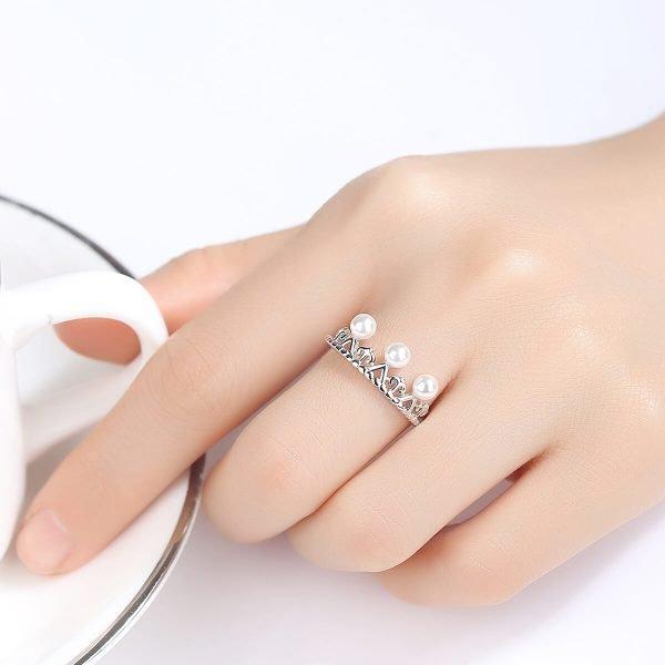 дамска ръка със сребърен пръстен под формата на корона с няколко малки перли
