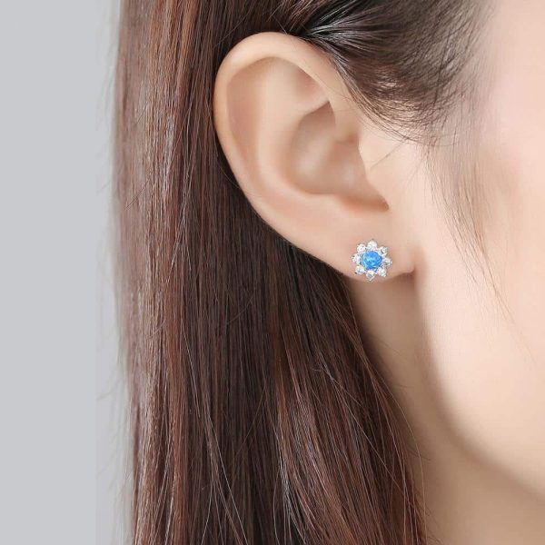 ladies model wearing silver earrings with floral motif and blue opal in the center