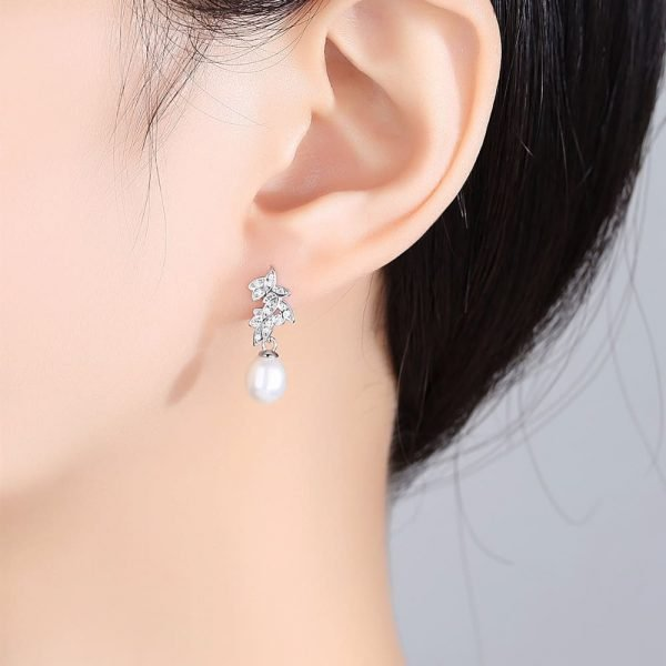 ladies model wearing dangling pearl earrings with floral motif and cubic zirconia