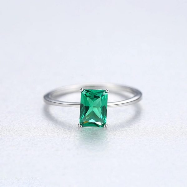 front shot of silver ring with rectangular green crystal