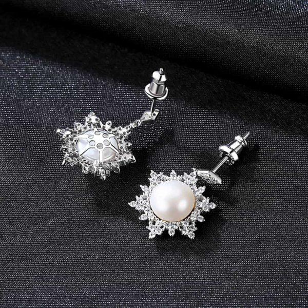 сребърни висящи обеци с масивна перла и заобикалящи я кубични циркони снимани от двете им страни