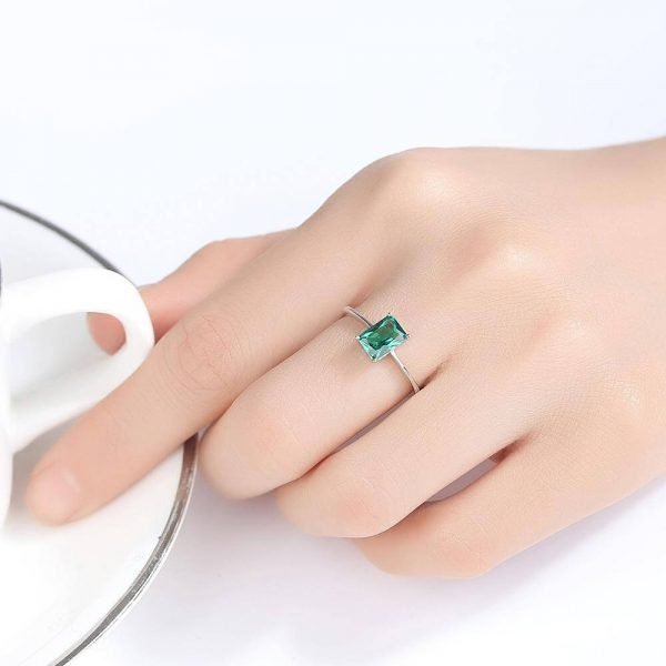 ladies model wearing silver ring with rectangular green crystal