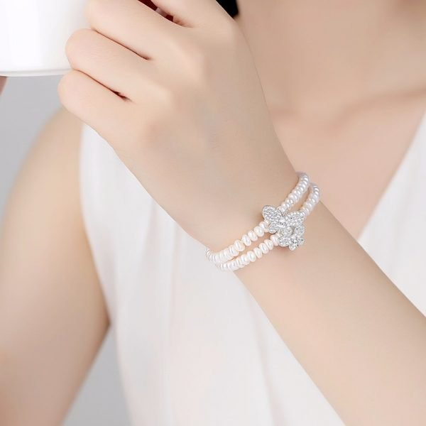 Ladies model with a double row pearl bracelet with two butterflies covered with cubic zirconia