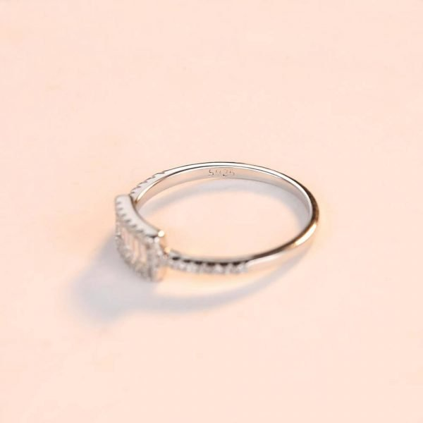clear silver ring with rectangular shape and multiple cubic zircons photographed at an angle on a white surface