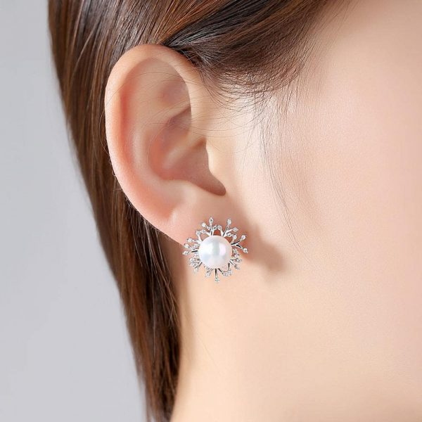 ladies model wearing silver pearl earrings with branches studded with cubic zirconia