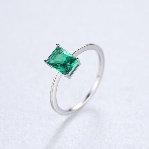 silver ring with rectangular green crystal photographed at an angle