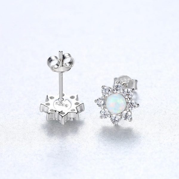 front and back of silver earrings with floral motif and light opal in the center