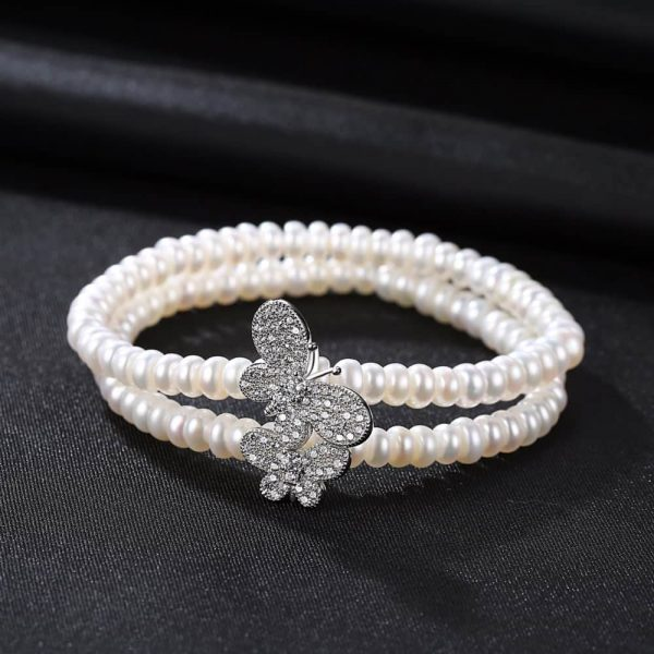double row pearl bracelet with two butterflies covered with zircons photographed frontally on black surface