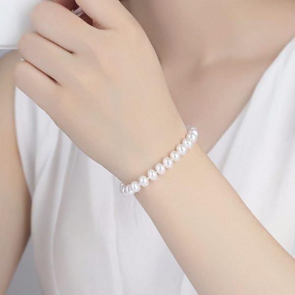 дамски модел носещ сребърна гривна с бели перли