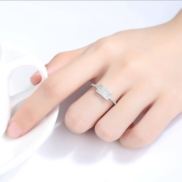 Ladies hand with clear silver ring with rectangular shape and multiple cubic zircons