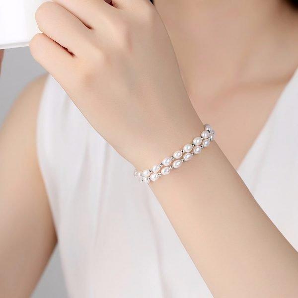 дамски модел носещ изящна сребърна гривна с два реда перли снимана отгоре