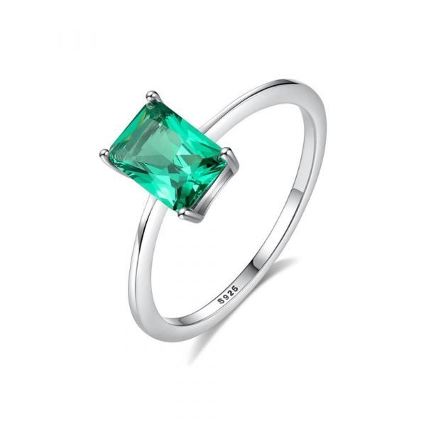 silver ring with rectangular green crystal photographed on white background