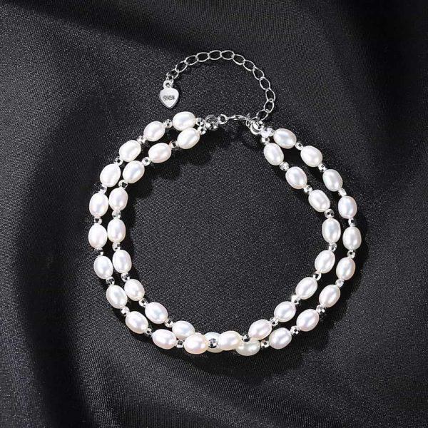 изящна сребърна гривна с два реда перли снимана отгоре върху черен фон