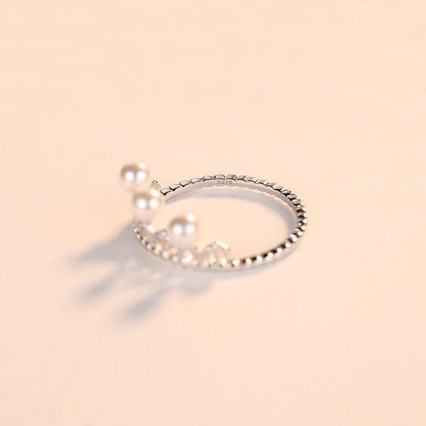 сребърен пръстен под формата на корона с няколко малки перли поставен върхо бяла повърхност
