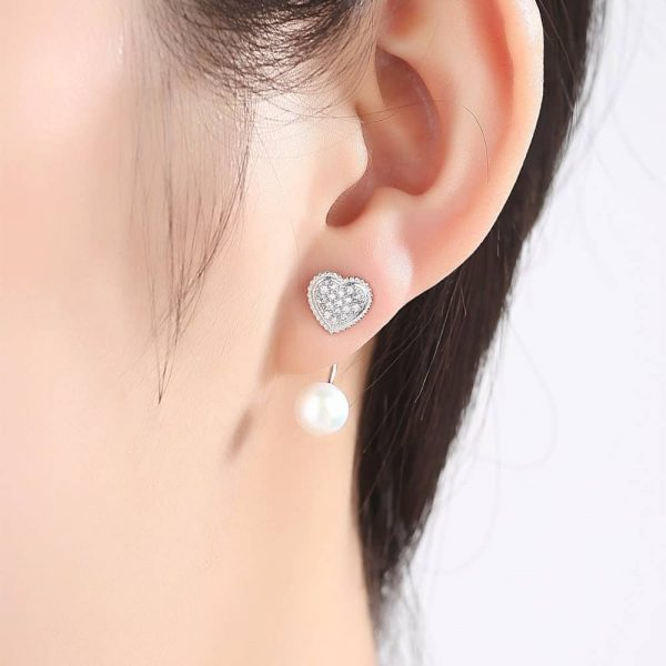ladies model with heart-shaped silver earrings with cubic zirconia and pearl below the level of the earlobe