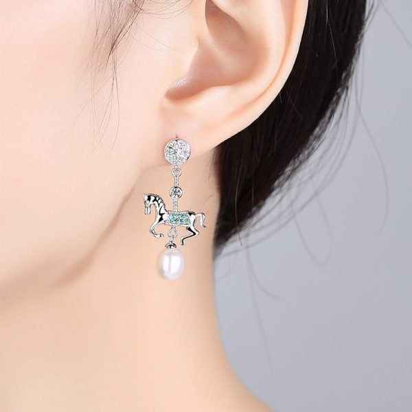 ladies model with hanging silver earrings with a pendant in the shape of a horse and a pearl under it