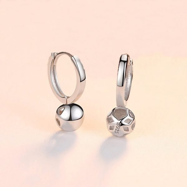 silver earrings rings with a globular element below the level of the ear placed on a white surface