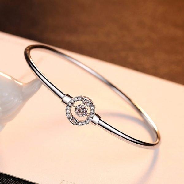 твърда сребърна гривна с кръгъл елемент и кубичен цирконий в средата снимана под лек ъгъл