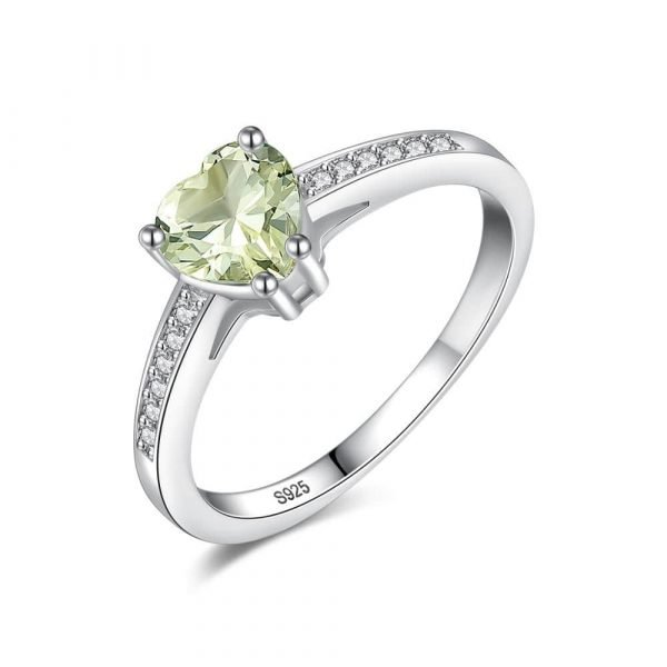 heart shaped silver ring with greenish crystal photographed on white background