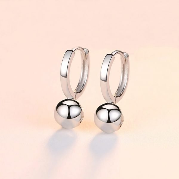 silver earrings rings with ball element below the ear level