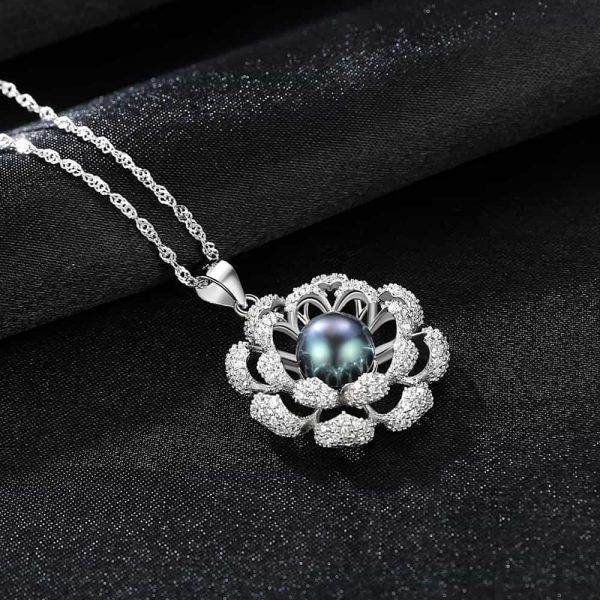 the back of a silver necklace with a floral motif and a dark blue Tahitian pearl photographed at an angle on a black surface