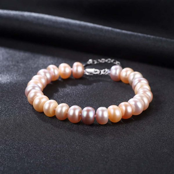 exquisite pearl bracelet with a pinkish tint of pearls photographed frontally on a black surface