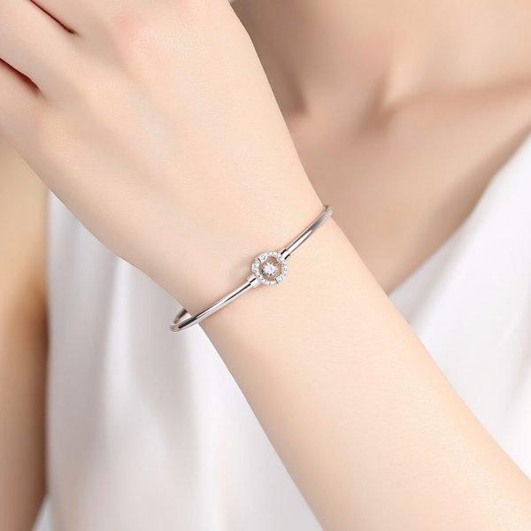 дамска ръка с твърда сребърна гривна и кръгъл елемент с кубичен цирконий в средата