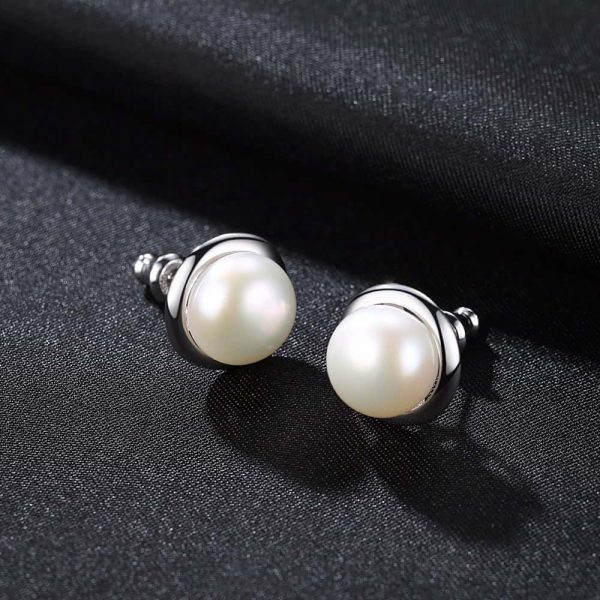 oval pearl earrings with silver screw circle photographed on black surface
