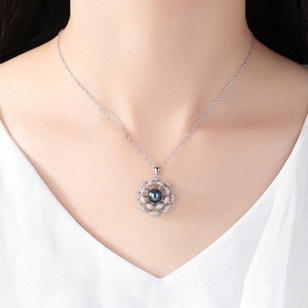 ladies model wearing the back of a silver necklace with a floral motif and a dark blue Tahitian pearl