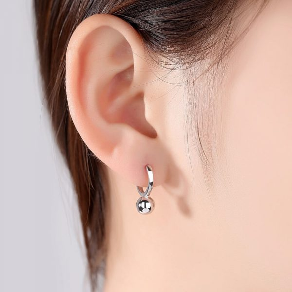 ladies model wearing silver earrings rings with a ball-shaped element below the ear level