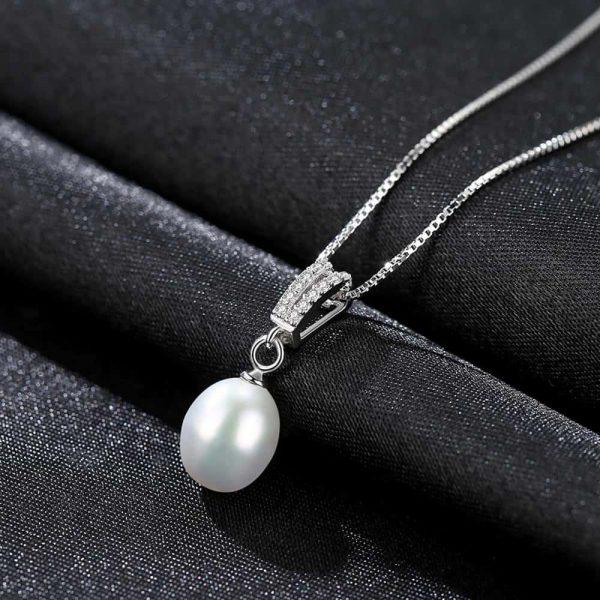 сребърно перлено колие с два реда циркони над перлата снимано под лек ъгъл на черна повърхност