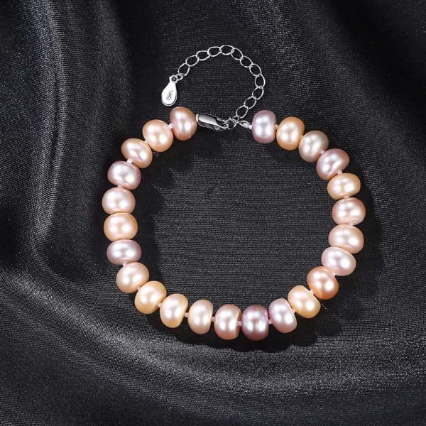 exquisite pearl bracelet with a pinkish tint of pearls photographed from above on a black surface