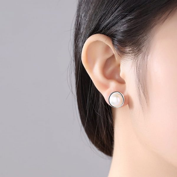ladies model with oval pearl earrings with silver circle on screw