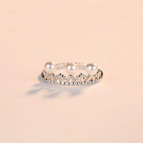 фронтална снимка на сребърен пръстен под формата на корона с няколко малки перли