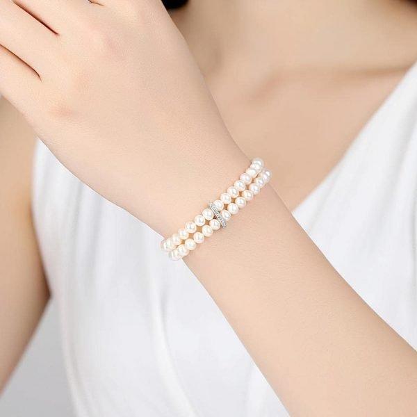 дамски модел носещ сребърна двуредова перлена гривна