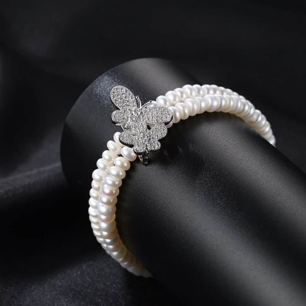 double row pearl bracelet with two butterflies covered with cubic zirconia on black stone